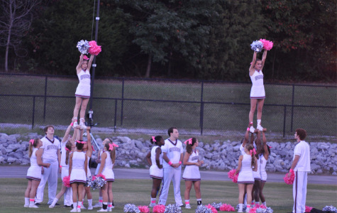 Cheerleaders practice out on the football field.