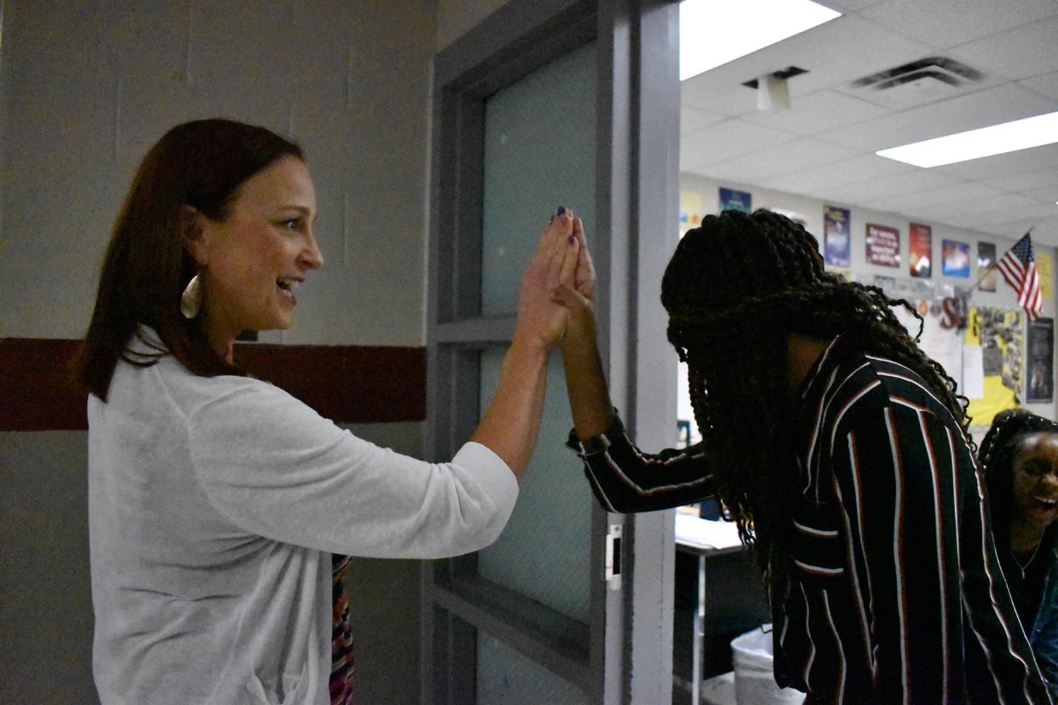 Mrs. Deborah Keller-Mitchell gives a high-five to one of her