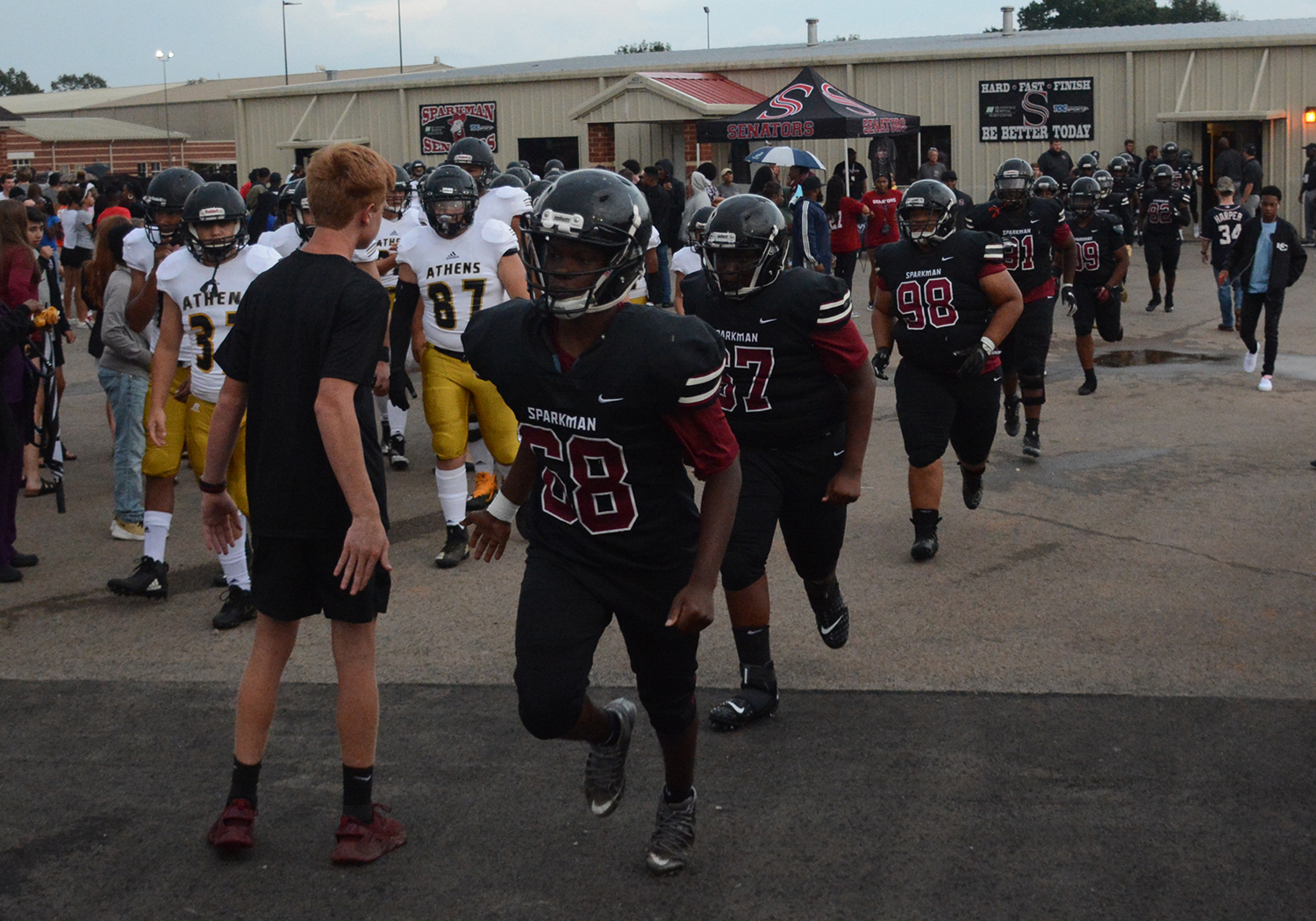 The football team takes the field after lightening delay. They defeated Athens 35-10 in the jamboree game.