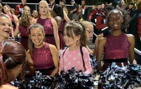 Sitting with the color guard at the James Clemens football game, 7-year-old Arabella Zapp enjoys her night.