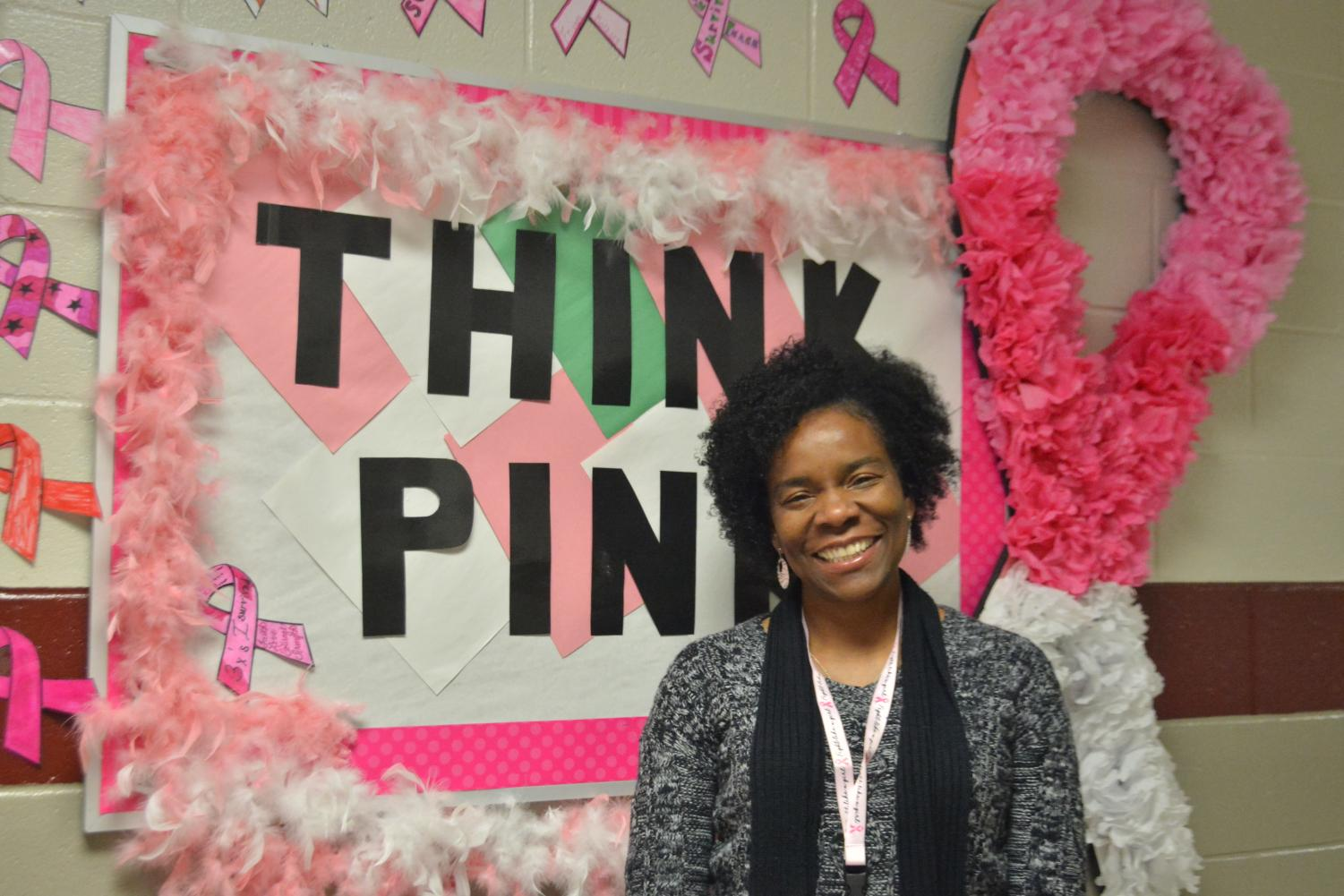 Aide Stacy Gilbert poses in front of the bulletin board created in the Sparkman Learning Community wing. Gilbert has received treatment for breast cancer three times.