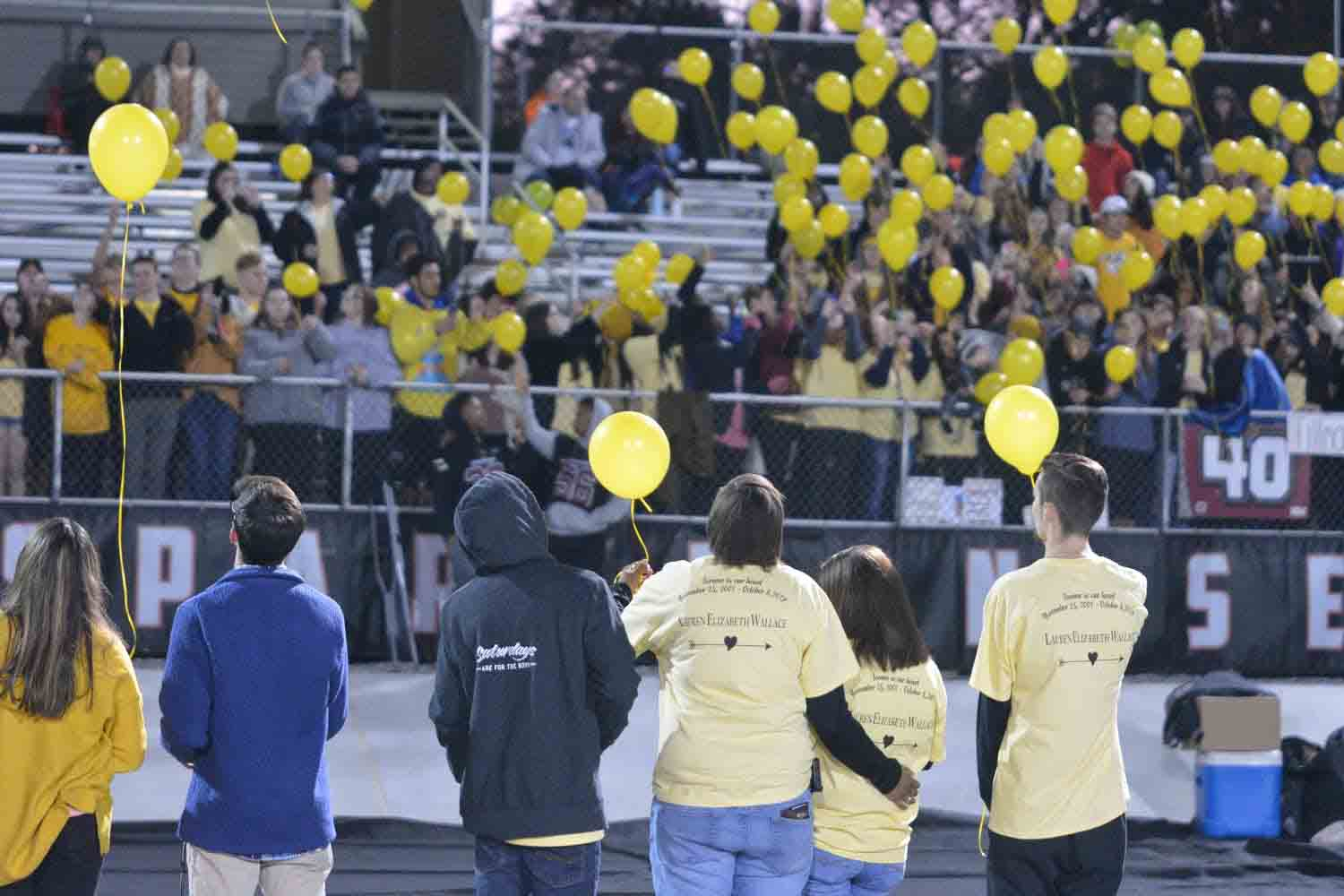 Members of the senior class stand on the football field before the Decatur kickoff to release balloons in honor of senior Lauren Wallace. Wallace lost her life in a car accident over fall break.