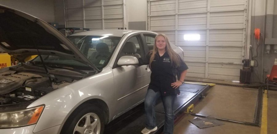 Posing by a car she worked on at Calhoun Community College, junior Kealey Weaver takes a break. Weaver takes a class at the local college to learn more about automotive mechanics.