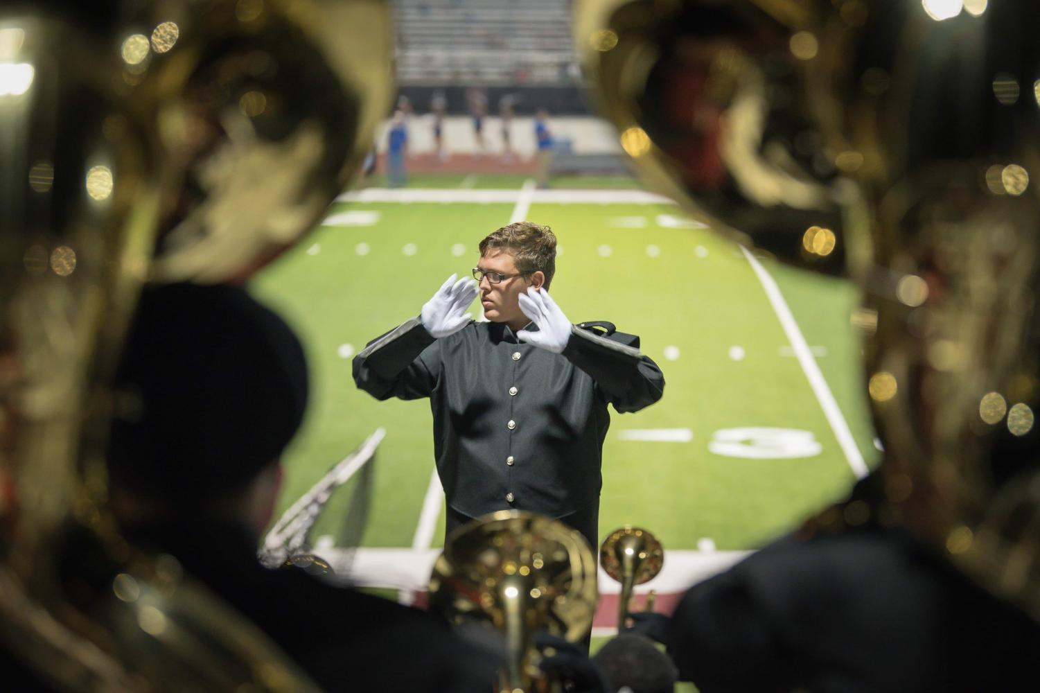 Leading the marching band at the game against Decatur, sophomore Kaden Burgess gets his first taste of directing music.