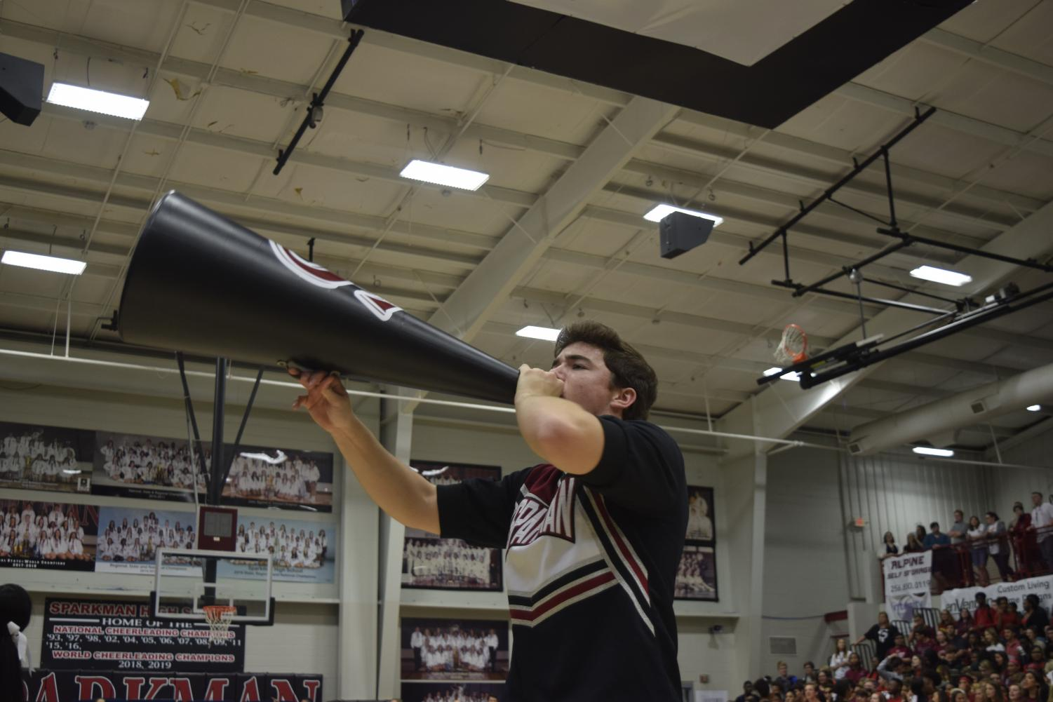 Junior Hayden Ottum chants cheers into the megaphone, bringing the team to victory at Regionals.
