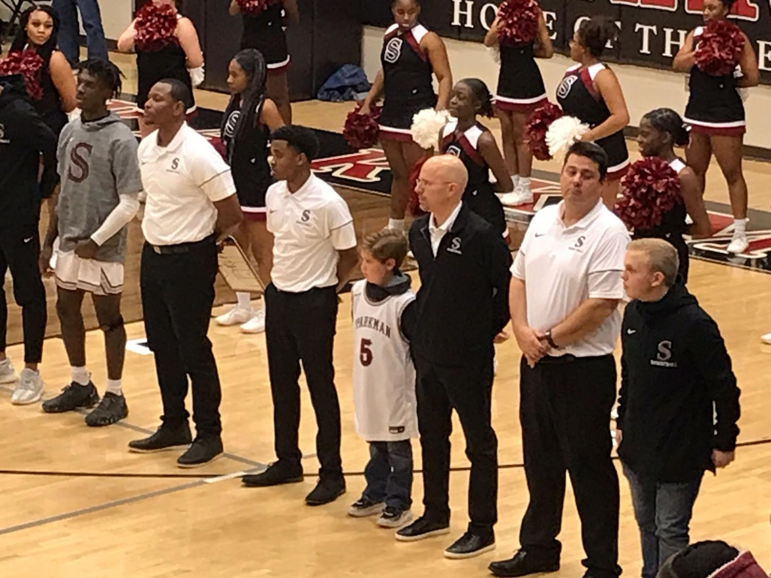 Monrovia Elementary student, Trey Hall, stands next to coach Jamie Coggins during the National Anthem.