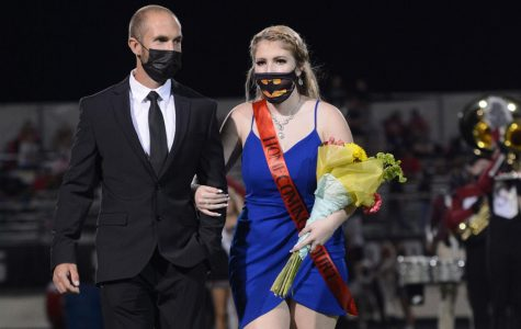 Junior Azlyn Miller walks across the field with her father during the Sept. 8 homecoming. Due to COVID, homecoming was conducted without students being in session.