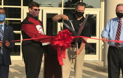 Principal Chris Shaw cuts the ribbon at Friday's ceremony opening the new Fine Arts Facility.