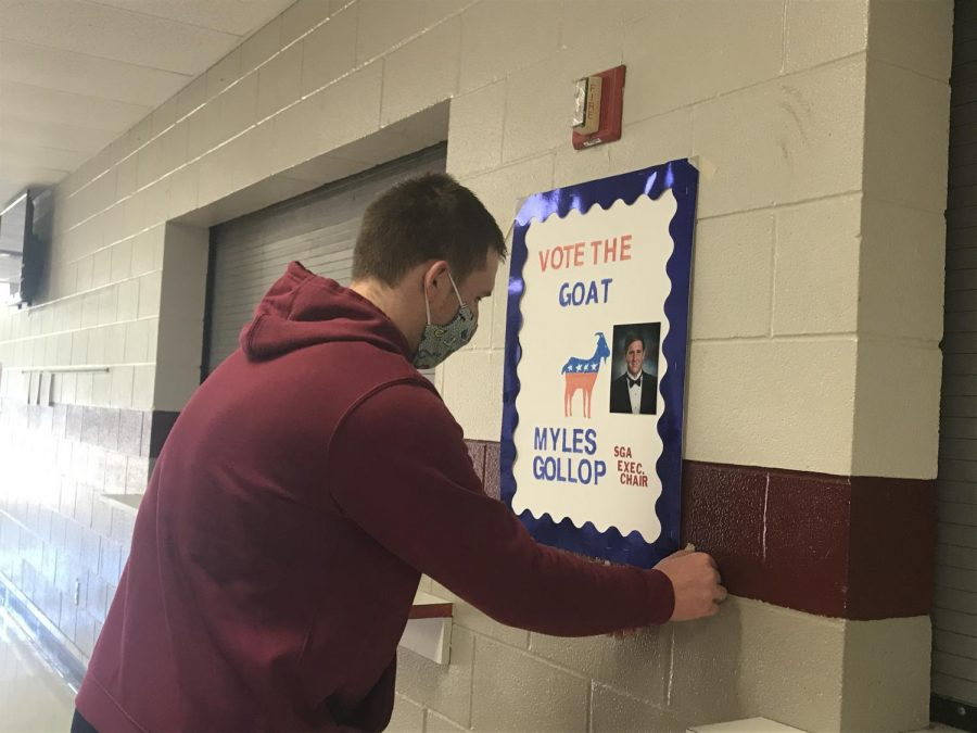 Senior Myles Gollop hangs up various campaign posters around the school. Gollop has spent a lot of time devoted to campaigning and reaching out to students.