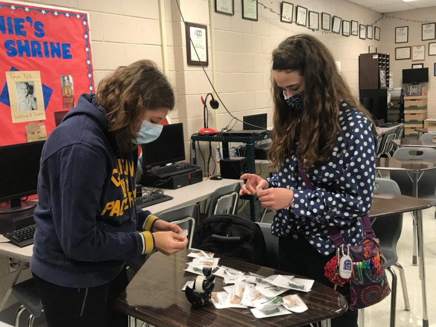 Putting together Veterans Day gifts for teachers, Ellie Ottum and Elsie Bradshaw stuff bags with toy soldiers. The Teens for Troops club has met two times to plan the year's activities.