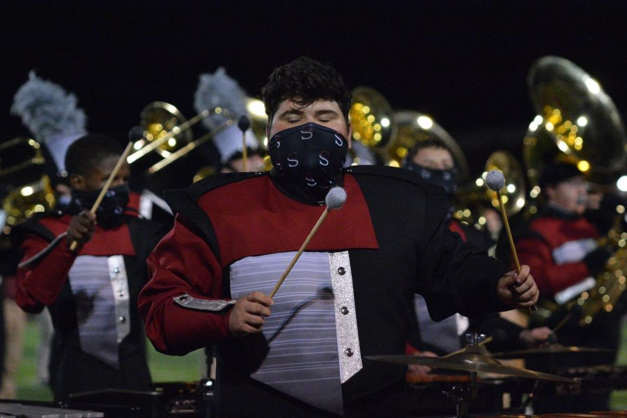 In the middle of the performance, senior Dylan Lancaster plays his instrument. The band performed their competition show at the last home football game of the year.