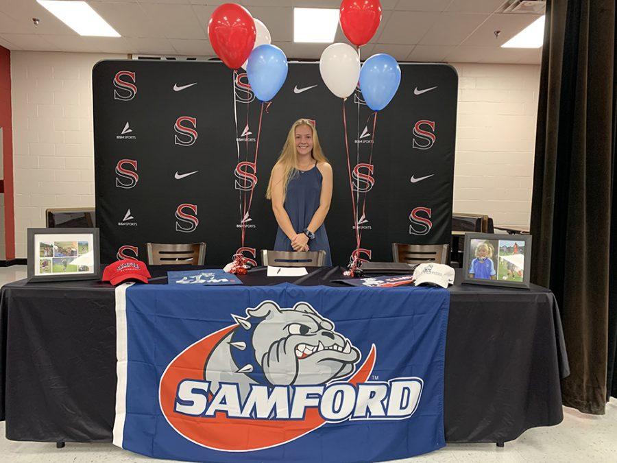 Before greeting her family and friends, senior Kellie Hovis poses for a quick photo to begin her signing ceremony.