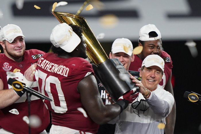 Coach Nick Saban gets help hoisting the 2020 National Championship trophy.