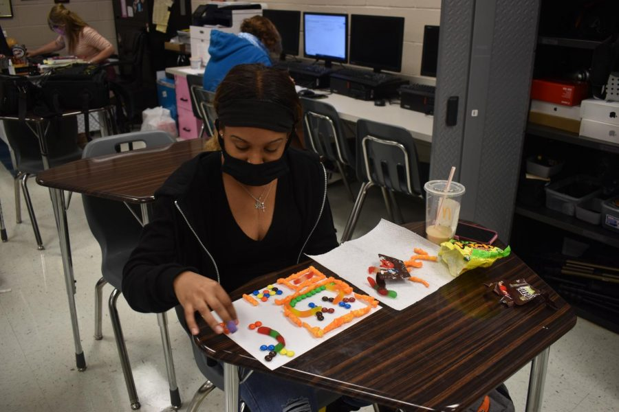 Yearbook co-editor Janiyah Blue uses food to work on design patterns.