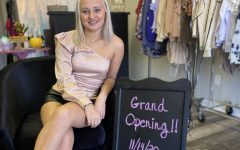 Stardust owner, Lexi Childers, poses with the grand opening sign.