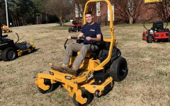 Controlling the lawnmower, senior Alden Hall works on completing his work.