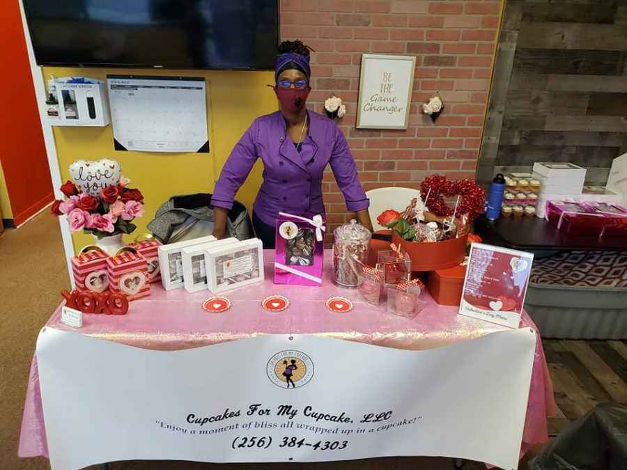 A representative from Cupcake for my Cupcake shows off a display of baked goods. The business is just one of many black-owned businesses thriving in the community.