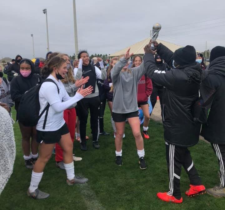 The girls soccer team accepts a trophy from the first tournament of the season.