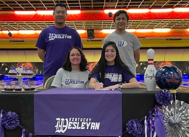 Senior Daylin Tolgo signs bowling scholarship with her family present. She held her signing at the Madison Bowling alley.