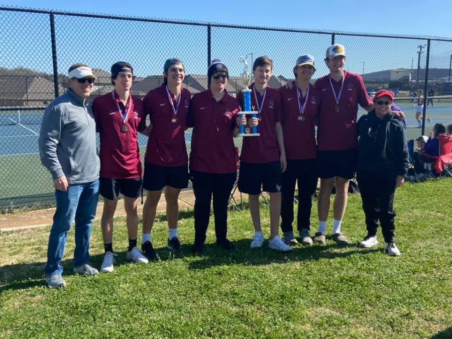 The boys tennis team poses with the trophy they won for being Madison County Champs.