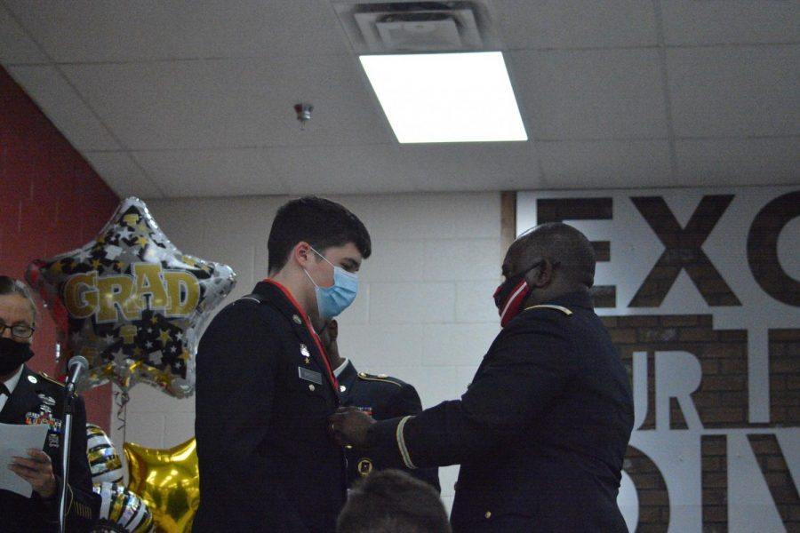 Senior Logan Barley receives his JRTOC award from Lt. Col. Nathan Lloyd at the annual JROTC senior night. Barley was accepted into West Point.