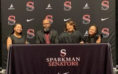 Coach Jarvis Wilson poses for a photo with his wife and daughters at the press conference announcing his hiring. Wilson has already begun working with the team.